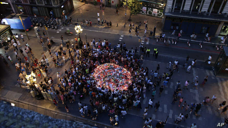 People gather at a memorial tribute of flowers, messages and candles to the victims on Barcelona's historic Las Ramblas promenade on the Joan Miro mosaic, embedded in the pavement where the van stopped after killing at least 13 people in Barcelona ,