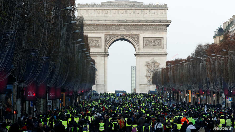 """Protesters wearing yellow vests walk on the Champs-Elysees Avenue with the Arc de Triomphe in the background during a national day of protest by the """"yellow vests"""" movement in Paris, Dec. 8, 2018."""