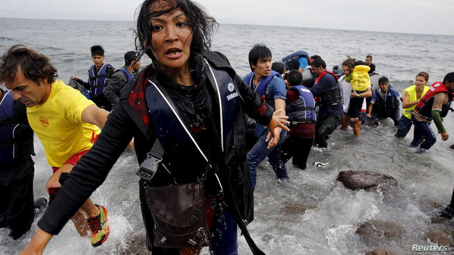An exhausted Afghan migrant frantically looks for her children as she arrives on the Greek island of Lesbos in an overcrowded dinghy after crossing a part of the Aegean Sea from the Turkish coast, Sept. 22, 2015.