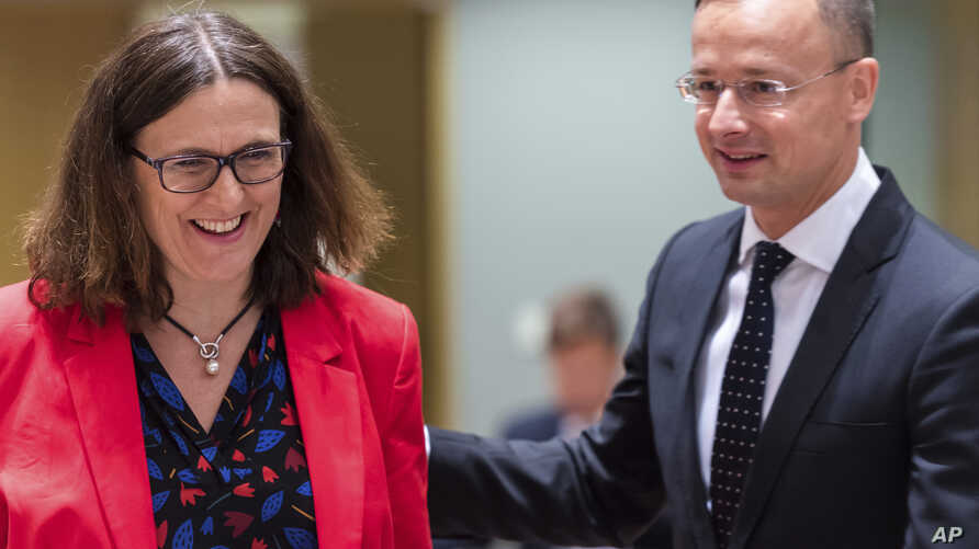 European Commissioner for Trade Cecilia Malmstrom, left, talks with Hungary's Foreign Minister Peter Szijjarto during an EU foreign affairs council on trade at the Europa building in Brussels, Belgium, May 22, 2018.