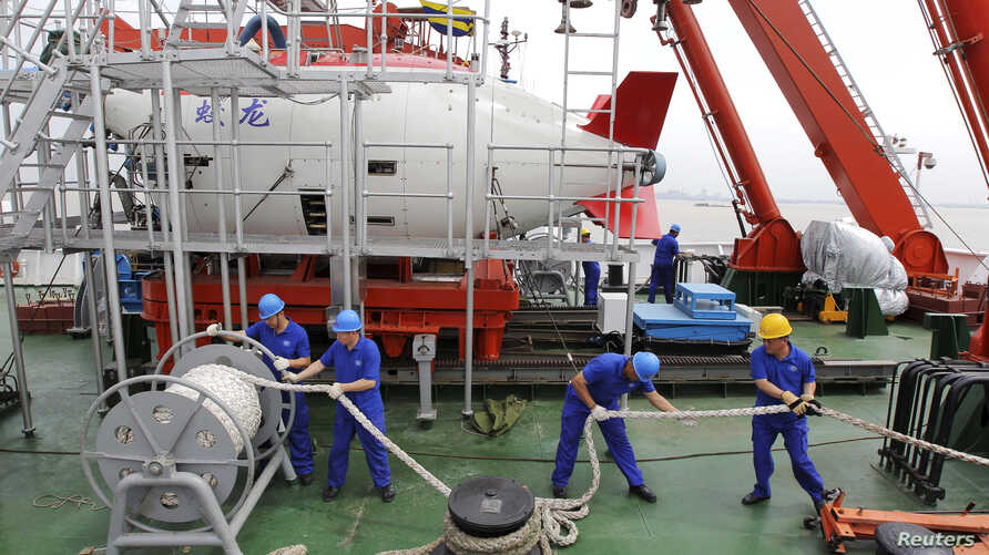 "FILE - Staff work on a boat in front of the China's manned deep-diving submersible ""Jiaolong"" in Jiangyin, Jiangsu province July 1, 2011."