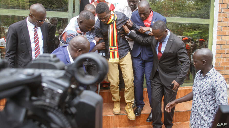 Uganda's prominent opposition politician Robert Kyagulanyi known as Bobi Wine (C) walks ahead of appearing at the general court martial in Gulu, northern Uganda on Aug. 23, 2018.