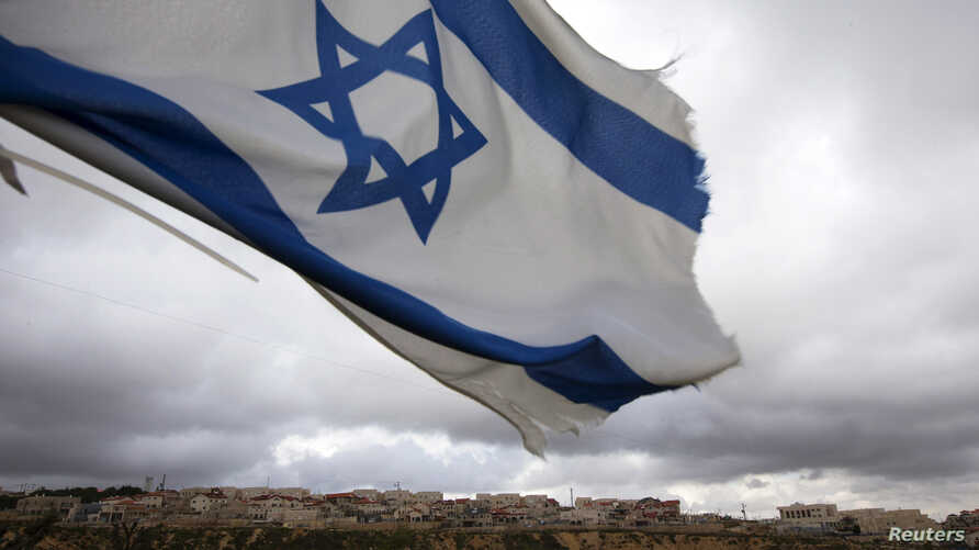 An Israeli flag flies on a hill near the West Bank Jewish settlement of Elazar, near Bethlehem March 17, 2013. U.S. President Barack Obama is due to make his first official visit to Israel and the Palestinian Territories this week, looking to improve