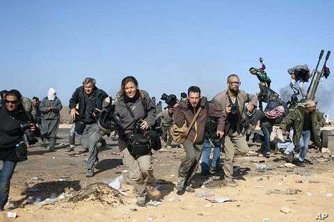 Journalists and photographers, including Hicks (R- in glasses) and Addario (far L), Moore (2nd L), Pickett (3rdL) and Poupin (4th L) run for cover during a bombing run by Libyan government planes at a checkpoint near the oil refinery of Ras Lanuf Mar