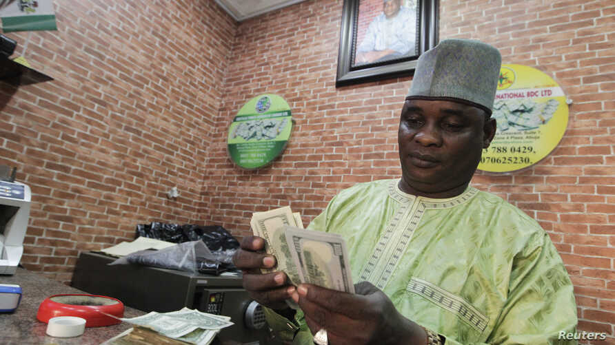 FILE - A bureau de change operator counts U.S. currency notes in Abuja, March 12, 2015.