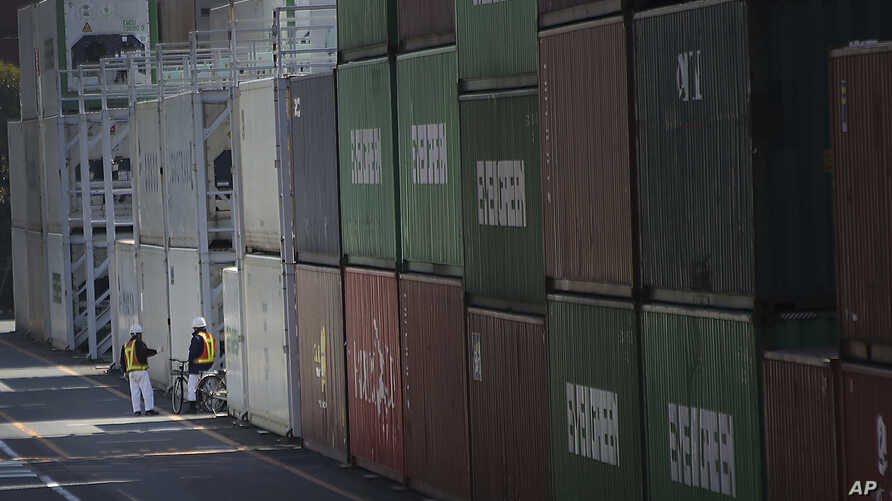 FILE - Port workers chat next to a pile of cargo at a container terminal in Tokyo, Feb. 19, 2015. Japan has recorded a trade surplus for September of 139.6 billion yen ($1.2 billion), but exports fell 1.2 percent from the previous year, marking the f