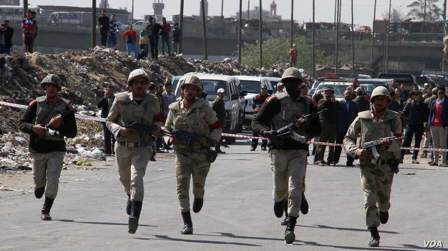 Egyptian military police soldiers run towards a checkpoint attacked by gunmen in Shubra al-Kheima, a suburb north of Cairo, Egypt, Saturday, March 15, 2014.