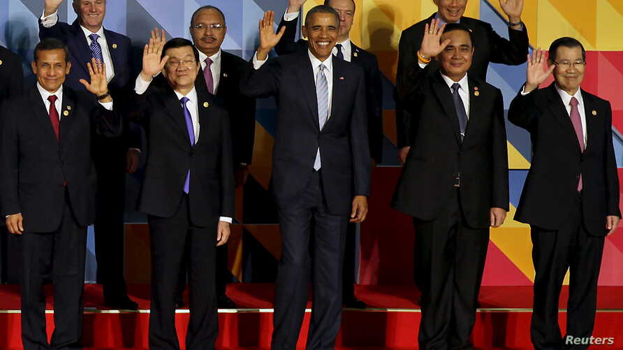 """U.S. President Barack Obama (C) and other leaders of the 21-member Asia-Pacific Economic Cooperation (APEC) summit wave to the media after an official """"family photo"""" in Manila, Nov. 19, 2015."""