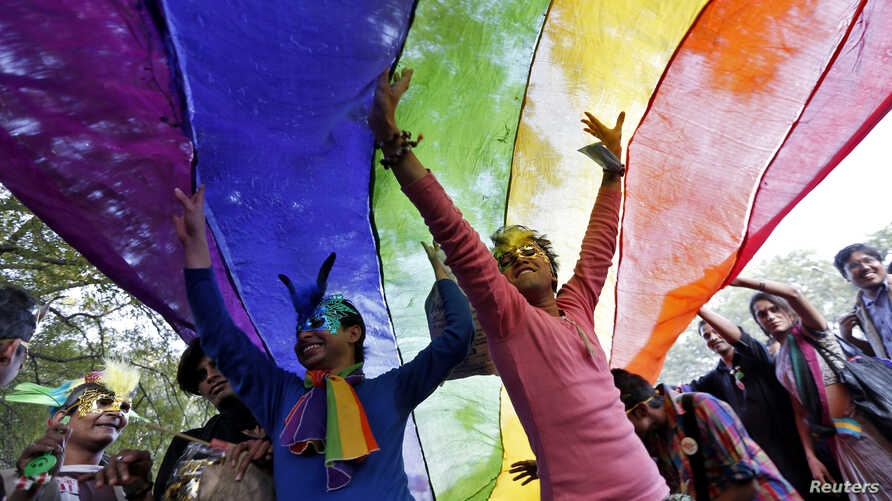 FILE - Participants dance under a a rainbow flag as they attend the sixth Delhi Queer Pride parade, an event promoting gay, lesbian, bisexual and transgender rights, in New Delhi, November 24, 2013.