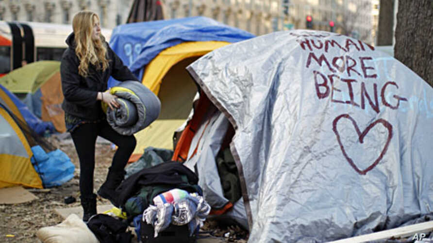 In compliance with new restrictions, an Occupy DC demonstrator packs up her camping gear at McPherson Square in Washington, January 30, 2012