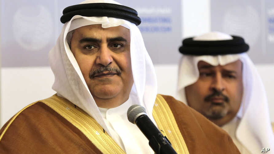 FILE - Bahraini Foreign Minister Sheik Khalid bin Ahmed Al Khalifa, left, listens to journalists while standing with Finance Minister Sheik Ahmed bin Mohammed Al Khalifa during a conference.