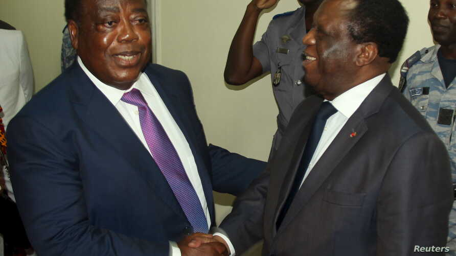 Charles Konan Banny (L), independent candidate for the 2015 presidential election, shakes hands with Independent Electoral Commission (CEI) President Youssouf Bakayoko (R) after registering his candidacy for the presidential election in Abidjan, Ivor...