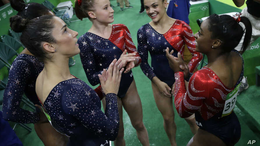 FILE - U.S. gymnasts, from left, Aly Raisman, Madison Kocian, Lauren Hernandez and Simone Biles wait for the score during the artistic gymnastics women's qualification at the 2016 Summer Olympics in Rio de Janeiro, Brazil, Aug. 7, 2016.