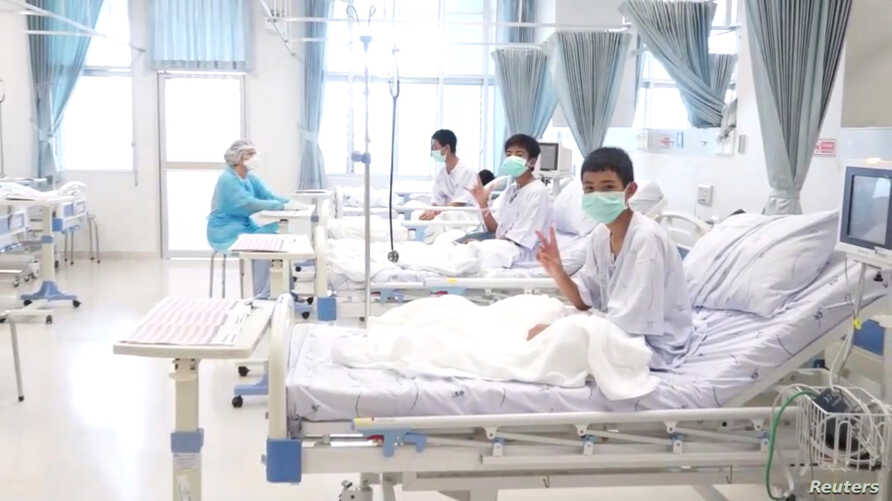 A screen grab shows boys rescued from the Thai cave wearing mask and resting in a hospital in Chiang Rai, Thailand from a July 11, 2018 handout video.  (Government Public Relations Department (PRD) and Government Spokesman Bureau/Handout via Reuters