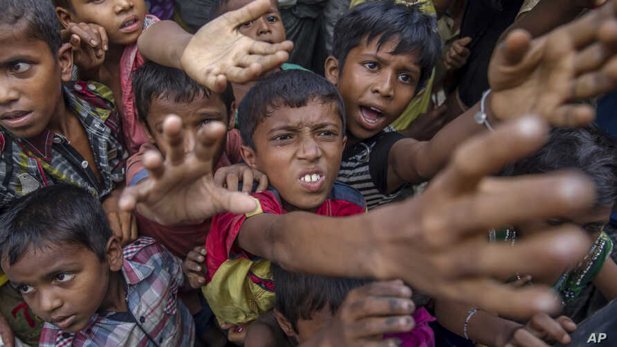 Rohingya Muslim children, who crossed over from Myanmar into Bangladesh, stretch out their arms out to collect chocolates and milk distributed by Bangladeshi men at Taiy Khali refugee camp, Bangladesh, Sept. 21, 2017.