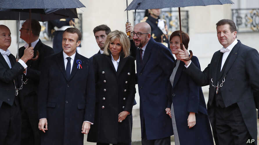Belgian Prime Minister Charles Michel, center, and his partner Amelie Derbaudrenghien, second right, are greeted by French President Emmanuel Macron, left, and his wife Brigitte Macron as they arrive at the Elysee Palace in Paris to participate in a