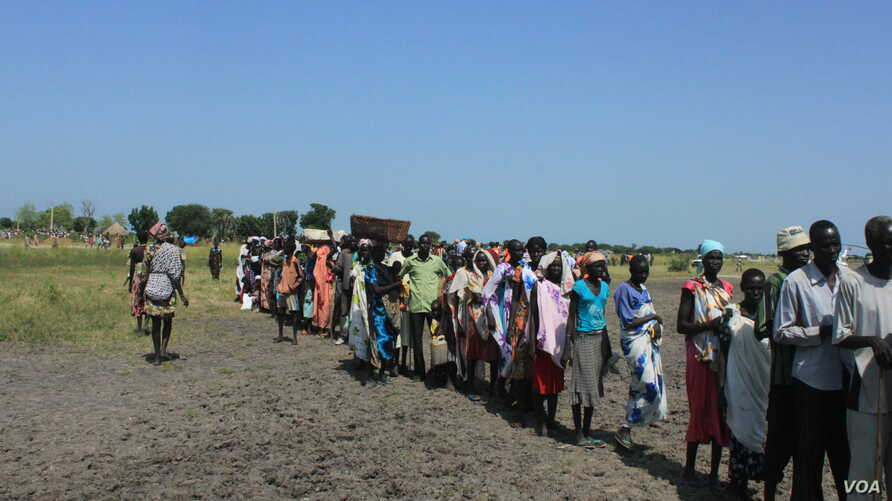 Hundreds of people wait in line in the town of Koch in South Sudan to receive food aid from the World Food Program on Friday, Aug. 25, 2015. Aid agencies stopped deliveries to Koch in May, after a sharp surge in violence there.