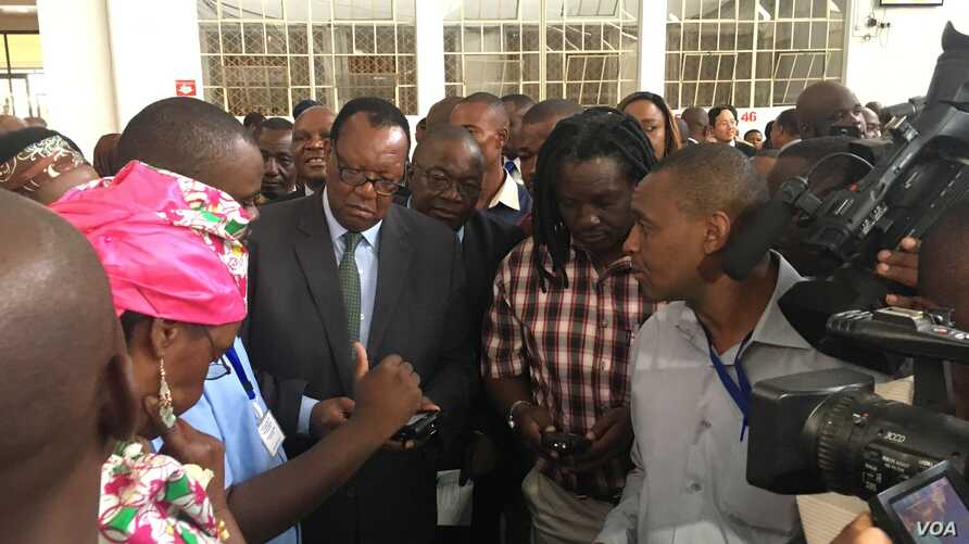 Zimbabwe Minister of Agriculture Joseph Made (in suit), who says the yield and quality of tobacco in 2017 are due to good rains – is shown how the new tobacco electronic auctioning system works, in Harare, March, 2017. (S. Mhofu/VOA)