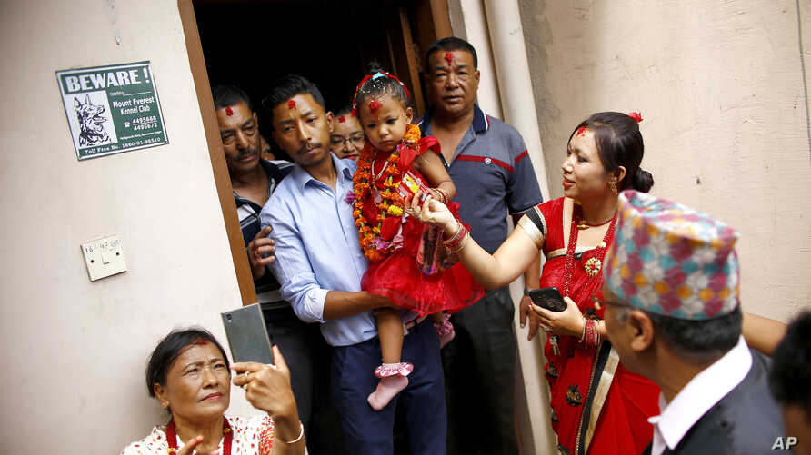 Nepal's new living goddess Trishna Shakya, 3, is carried by her father as they leave home for a temple palace in Kathmandu, Nepal, Sept. 28, 2017.