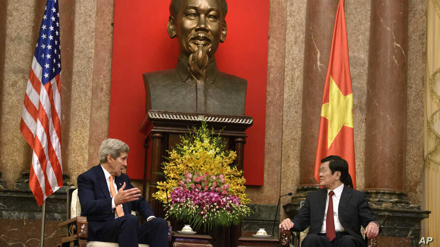 U.S. Secretary of State John Kerry, left, and Vietnamese President Truong Tan Sang talks during a meeting at the Presidential Palace in Hanoi, Vietnam, Friday, Aug. 7, 2015.