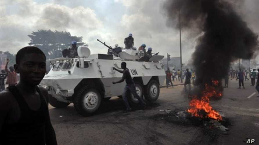 UN peacekeepers drive past supporters of Alassane Ouattara as they demonstrate and burn tires in the Abobo neighbourhood in Abidjan, February 19, 2011