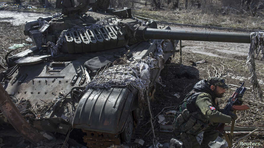 A pro-Russian rebel crouches in front of a destroyed Ukranian army tank in the village of Spartak, on the outskirts of Donetsk, March 16, 2015.