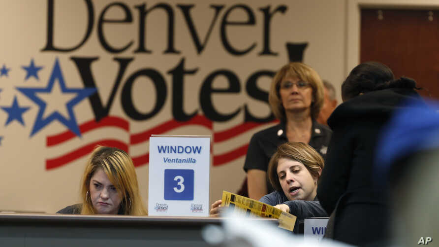 FILE - An election judge helps a voter with a question about the ballot at the Denver Elections Division, in Denver, Colorado, Nov. 6, 2018.