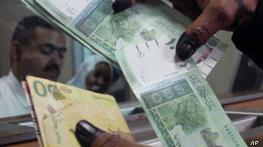 A woman displays Sudan's new currency at the central bank in Khartoum, Sudan. The Sudanese government began circulating a new edition of the Sudanese pound on Sunday as a precautionary measure following the loss of oil revenues resulting from South S