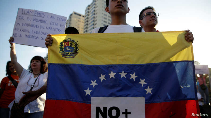 """An opposition supporter holds a Venezuelan flag with a sign that reads """"No more dictatorship"""" during a protest against Venezuelan President Nicolas Maduro's government, in Caracas, March 30, 2017."""