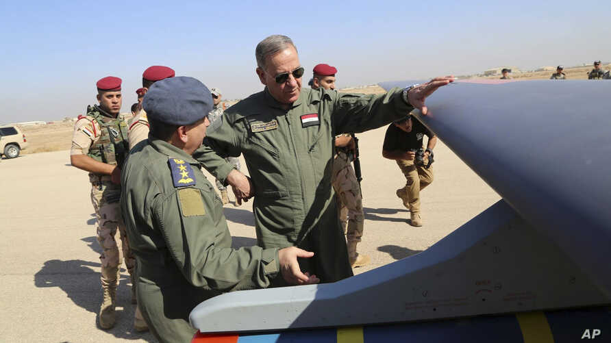 In this Oct. 10, 2015, Iraqi Defense Minister Khaled al-Obeidi, center, inspects a first Chinese drone to be used by the Iraqi Air Force before sending it to bomb Islamic State group positions at an airbase in Kut.