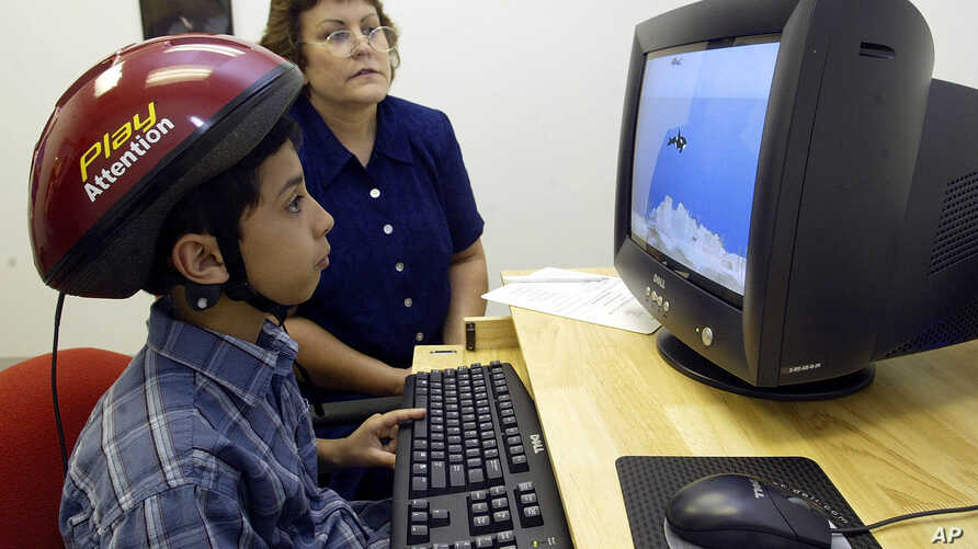FILE - An 8-year-old boy concentrates on a computer screen as he uses a special helmet — an ADHD intervention device — with an instructor's help at a learning center in Greensboro, N.C.