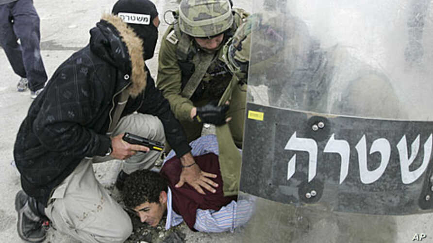A plainclothes Israeli police officer and soldiers detain a Palestinian protester during clashes near the Qalandiya checkpoint between Ramallah and Jerusalem, Sunday, May 15, 2011
