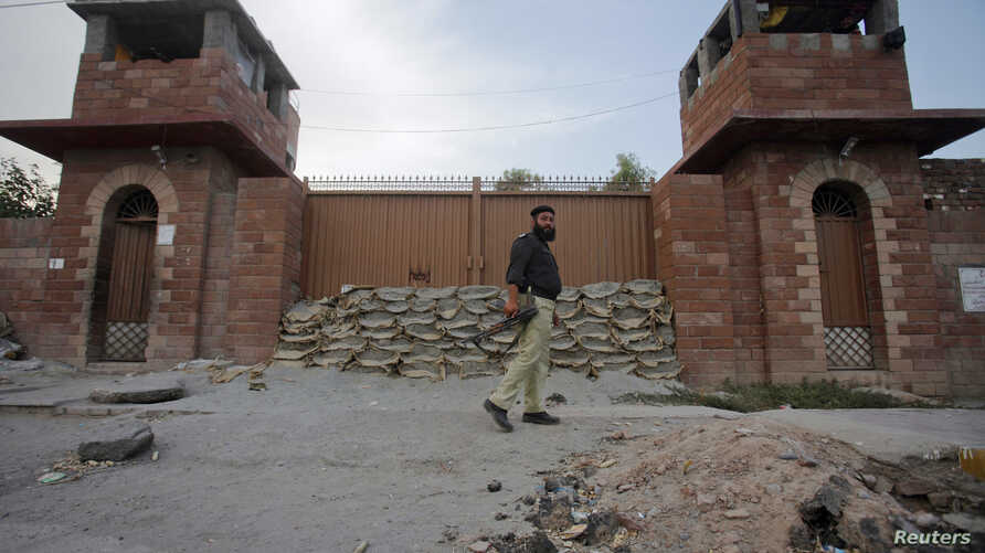 A police officer walks past Central Jail in Peshawar June 21, 2012. Pakistani authorities have sentenced Pakistani doctor Shakil Afridi, accused of helping the CIA find Osama bin Laden to 33 years in jail on charges of treason, officials said, a move