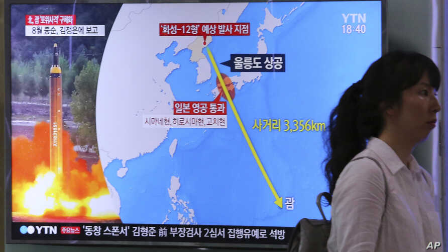 A woman passes by a TV screen showing a local news program reporting on North Korea's threats to strike Guam with missiles at the Seoul Train Station in Seoul, South Korea, Aug. 10, 2017.
