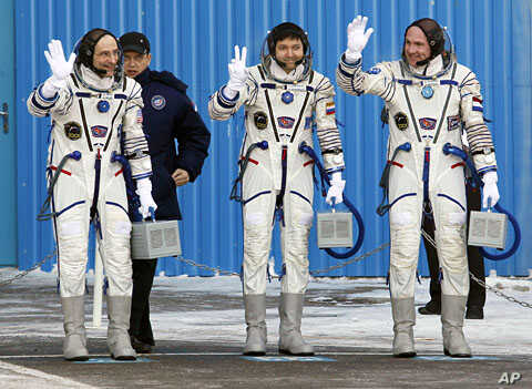 U.S. astronaut Donald Pettit (L), Russian cosmonaut Oleg Kononenko (C) and Dutch astronaut Andre Kuipers, members of the International Space Station (ISS) crew, wave before the launch of the Soyuz TMA-03M spacecraft at Baikonur cosmodrome, December 2