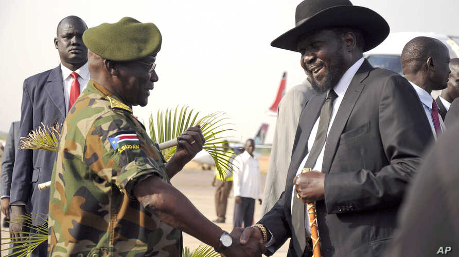 FILE - South Sudan's President Salva Kiir (R) is received by Chief of General Staff of the Sudan People's Liberation Army (SPLA) Paul Malong Awan at the airport in Juba, March 6, 2015, upon arriving after attending peace talks with rebel leader Riek