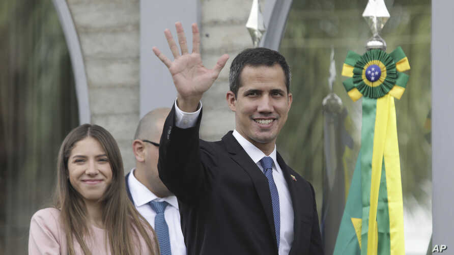 Venezuela's self-proclaimed interim president Juan Guaido waves at the press as he arrives for a meeting with ambassadors and representatives from European Union, in Brasilia, Brazil, Feb. 28, 2019.
