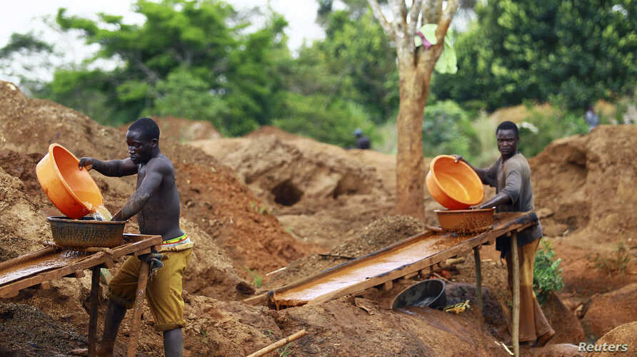 FILE - Gold miners sift through sandy soil as they work at an excavation site at a small scale mine in Bugiri, 348 km (216 miles) east of Kampala, Uganda's capital, Feb. 5, 2013.