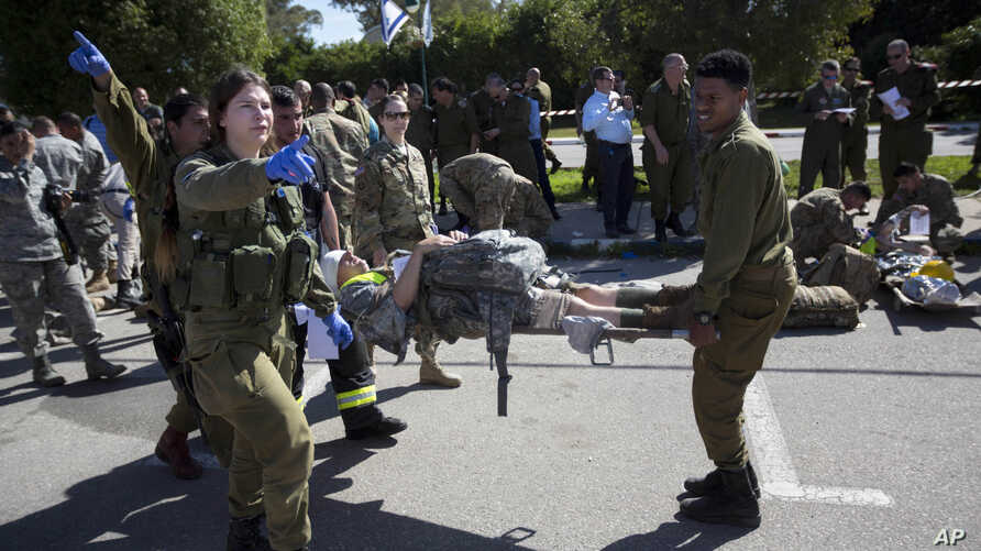 File - In this March 1, 2016 photo, American servicemen and Israeli soldiers participate in a joint drill simulating a rocket attack at a base in Hatzor, central Israel. Israel is making contingency plans to evacuate up to a quarter million people fr
