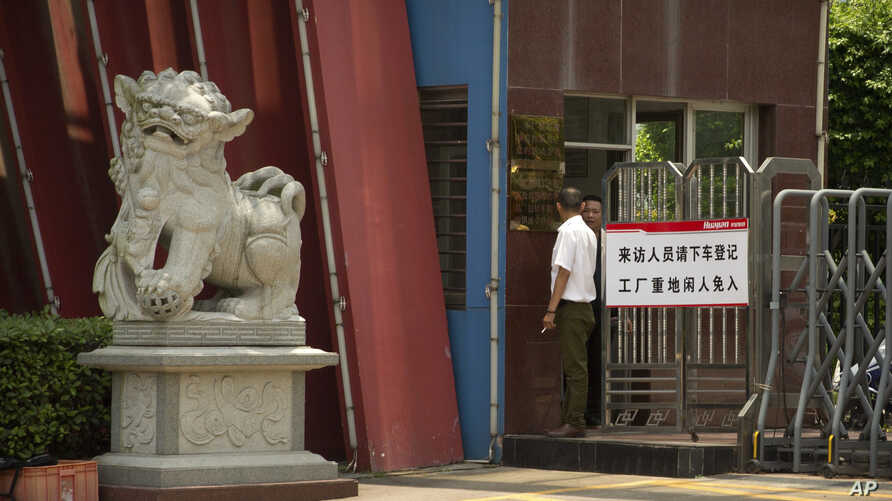 A man stands at the entrance gate of a Huajian Group shoe factory in Ganzhou, in southeastern China's Jiangxi Province, June 6, 2017.