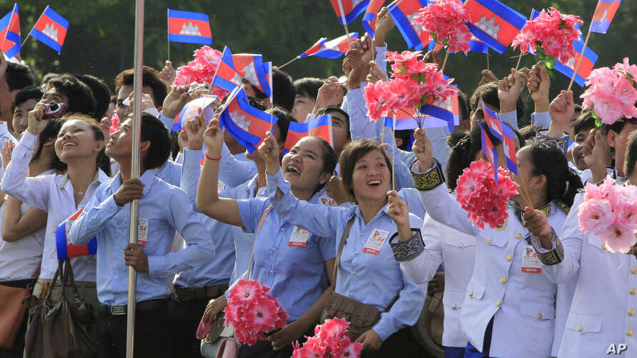 FILE - Cambodian students are seen waving national flags during Independence Day celebrations in Phnom Penh.