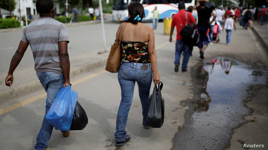 File - People cross to Venezuela over the Simon Bolivar bridge after shopping in Cucuta, Colombia, Dec. 1, 2016. Many Venezuelan women are selling their hair in Colombia in reaction to their country's struggling economy.