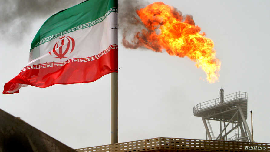 FILE - A gas flare on an oil production platform in the Soroush oil fields is seen alongside an Iranian flag in the Persian Gulf, Iran, July 25, 2005.
