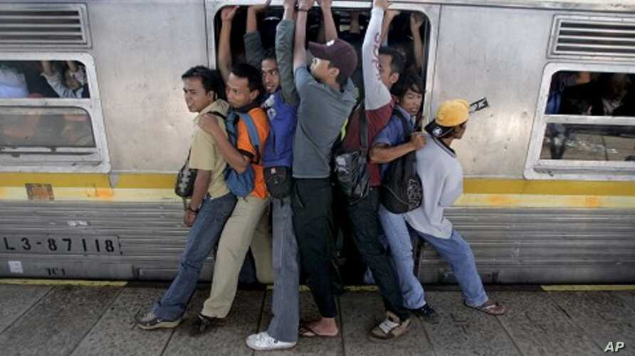 Indonesian men struggle to board a packed commuter train at a station in Jakarta, May 11, 2010.