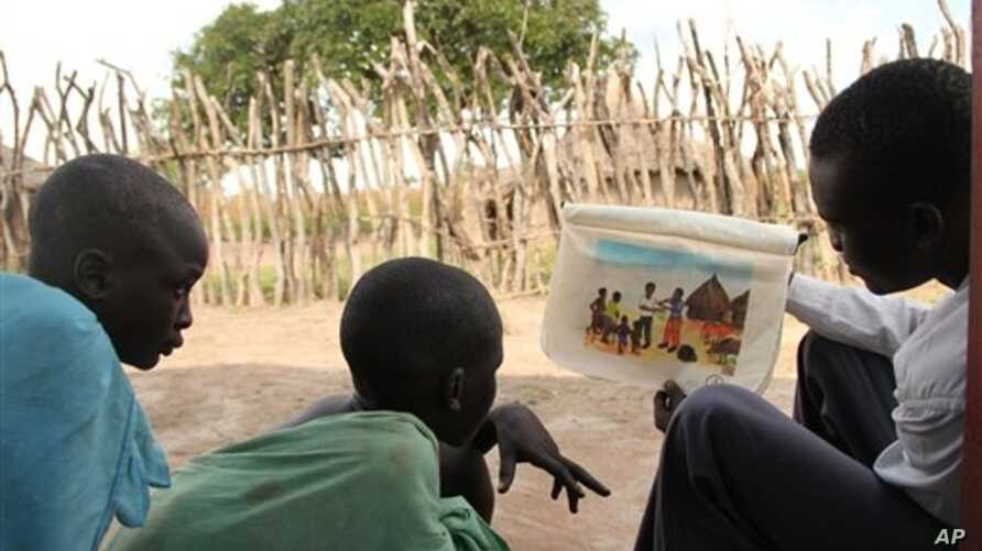 Isaiah Deng Mayom, right, Carter Center field officer, uses a flip chart to show children how to avoid contracting guinea worm, Lakes State, Sudan, Nov. 4, 2010.