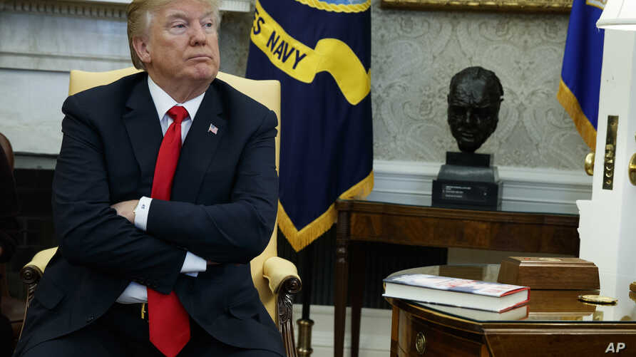 President Donald Trump listens during a meeting with North Korean defectors where he talked with reporters about allowing the release of a secret memo on the FBI's role in the Russia inquiry, in the Oval Office of the White House, Feb. 2, 2018, in Wa...