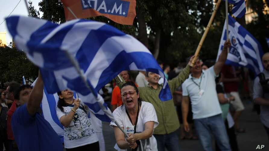 A supporter of the No vote waves a Greek flag after the referendum's exit polls at Syntagma square in Athens, Sunday, July 5, 2015.