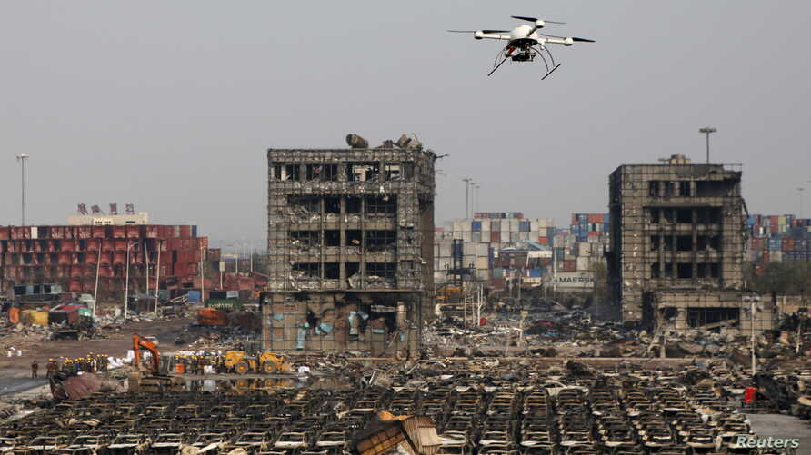 A drone operated by paramilitary police flies over the site of last week's explosions at Binhai new district in Tianjin, China, August 17, 2015.