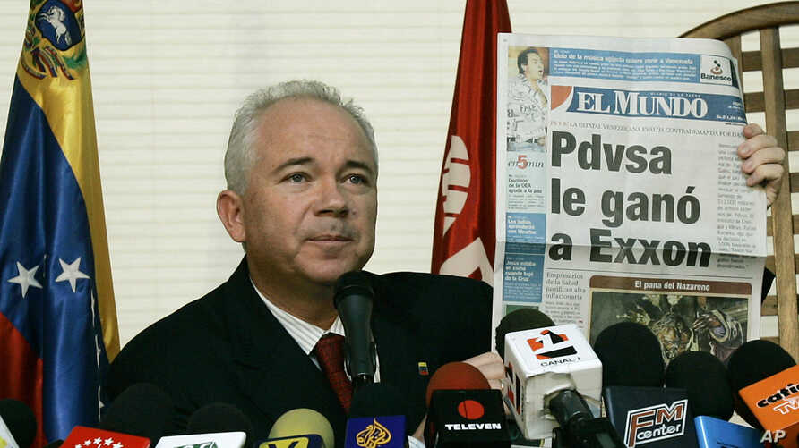 """FILE - Venezuela's Oil Minister Rafael Ramirez shows to the media in Caracas a newspaper, which reads in Spanish """"PDVSA defeats Exxon""""."""
