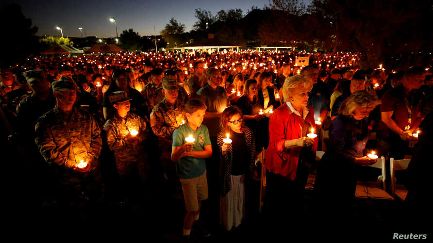 People hold candles during a memorial service for Charleston Hartfield, an off-duty Las Vegas police officer who was killed during the Route 91 music festival mass shooting, in Las Vegas, Nevada, Oct. 5, 2017.